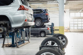 modern workshop with automobiles raised on car lifts on blurred foreground