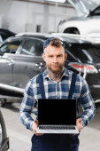 mechanic holding laptop with blank screen near automobiles on blurred background