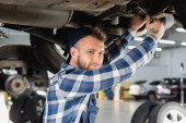 mladý mechanik dívá na kameru při kontrole spodní části zvýšeného vozu