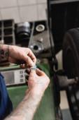 részleges kilátás mechanikus eltávolítása fém kiegyensúlyozó lemez ragasztószalag közelében egyensúly szabályozó gép elmosódott háttér