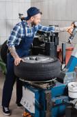 mladý mechanik pracující s náhradním strojem pneumatik v dílně