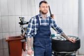 Junger Mechaniker in Overalls steht neben Rad an Reifenersatzmaschine in Werkstatt