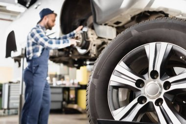 Close up view of wheel near mechanic repairing wheel hub on blurred background stock vector