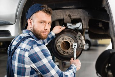 Young mechanic looking at camera while adjusting wheel hub on blurred background stock vector