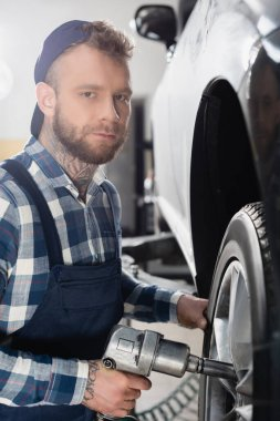 Young mechanic looking at camera while fixing car wheel with pneumatic wrench stock vector