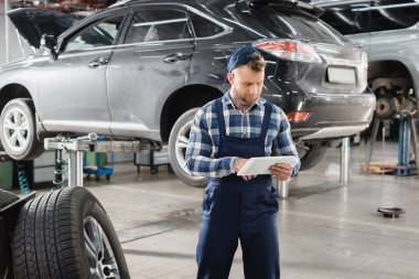 Technician in uniform using digital tablet near vehicle raised on car lift stock vector
