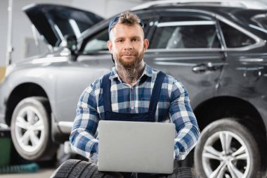Young mechanic looking at camera while using laptop near car on blurred background stock vector