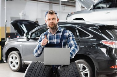 Repairman showing thumb up while holding laptop neat cars on blurred background stock vector