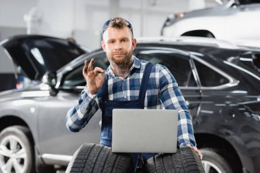 Technician showing okay gesture while holding laptop near cars on blurred background stock vector