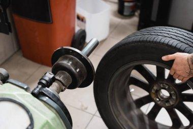 Cropped view of mechanic holding wheel near balance control machine stock vector