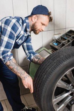 Young repairman examining wheel on balance control equipment stock vector