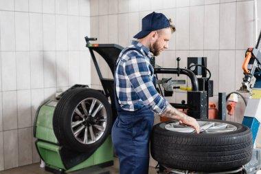 Repairman in overalls putting wheel on tire changing machine in workshop stock vector
