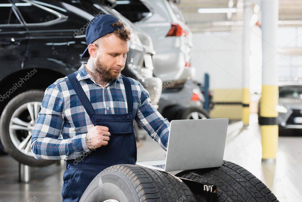 giovane tecnico che lavora su laptop vicino alle auto in officina su sfondo sfocato