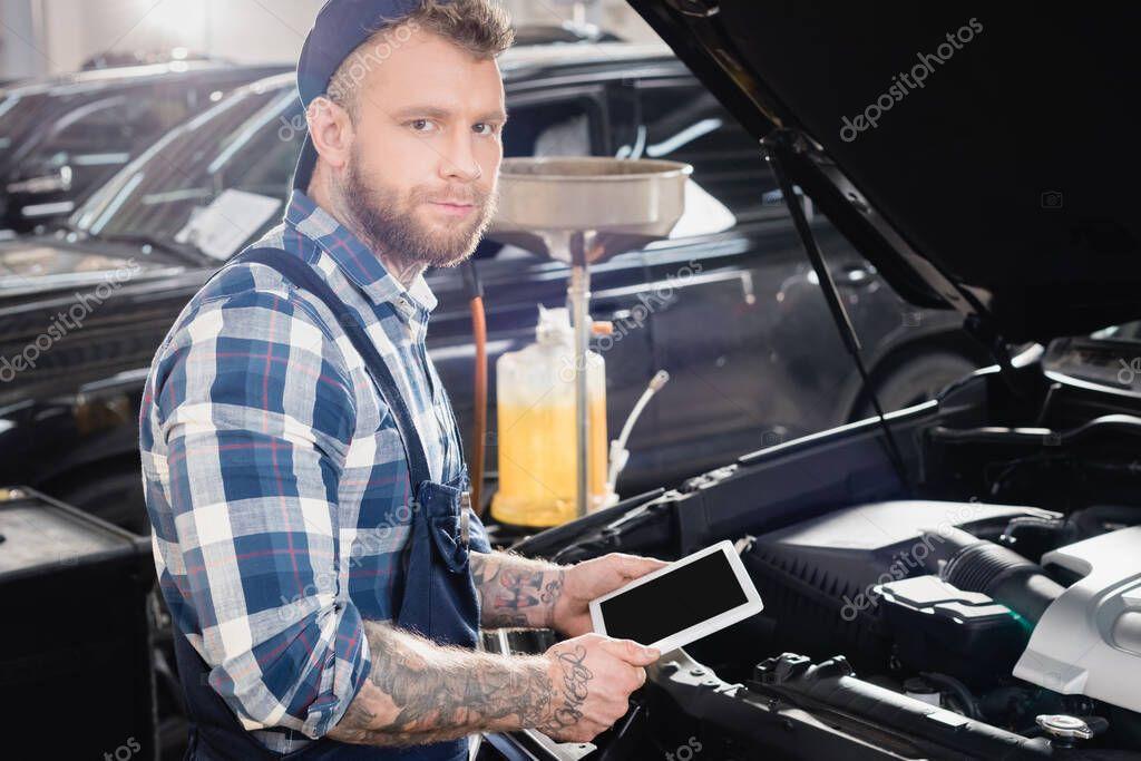 giovane riparatore con tablet digitale vicino al vano motore dell'auto
