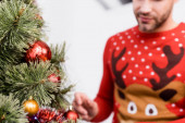 cropped view of bearded man in sweater decorating christmas tree on blurred foreground