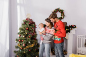 happy woman holding in arms baby boy near cheerful husband and decorated christmas tree