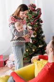 usmívající se žena držení v náručí kojenec poblíž manžela a vánoční strom na rozmazaném pozadí