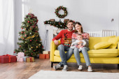 happy family with baby boy sitting on sofa near christmas tree