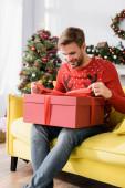 šťastný muž v červeném svetru při pohledu na zabalený dárek, zatímco sedí na pohovce s rozmazané vánoční strom na pozadí