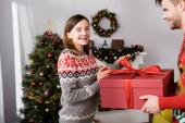 veselý muž v červeném svetru držení zabalené dárek v blízkosti šťastný manželka a vánoční strom na rozmazaném pozadí