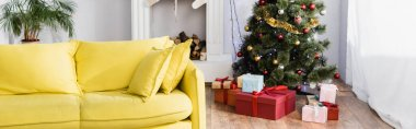 Wrapped presents under christmas tree in decorated and modern living room, banner stock vector