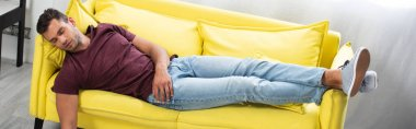 Young man sleeping on yellow couch at home, banner stock vector