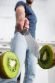 Close up view of wet knife near halves of juicy kiwi with man on blurred background