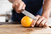 Cropped view man holding orange and knife on wooden board on blurred background