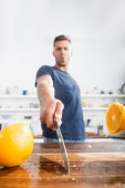 Close up view of halves of orange on wet cutting board and knife in hand of young man on blurred background