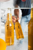 Wet bottle of beer in hand of man near open fridge on blurred background