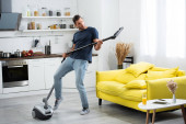 Excited man having fun while holding brush of vacuum cleaner at home