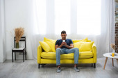 Man using smartphone on couch near glass of orange juice on coffee table
