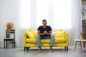 Izgalmas férfi kezében okostelefon, miközben nézi a kamera a kanapén