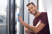 Smiling man cleaning window with rag and detergent at home