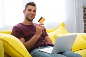 Cheerful man holding credit card and laptop on blurred foreground at home