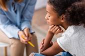 Közelkép a feldúlt afro-amerikai lány csukott szemmel pszichológus közelében konzultáció során elmosódott háttér