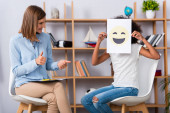 Smiling psychologist with thumbs up looking at african american girl covering face with happy expression on paper during consultation