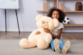 Rozrušený africký americký dívka s autismem při pohledu na kameru a objímání medvídek zatímco sedí na podlaze s rozmazané kanceláře na pozadí