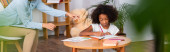 Pszichológus ujjal mutogat az albumra közel afro-amerikai lány rajz színes ceruzák elmosódott előtérben, banner