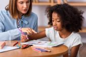 Pszichológus ujjal mutogat a képre közel afro-amerikai lány színes ceruzával dohányzóasztal homályos háttér