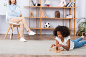 Konzentrierte afrikanisch-amerikanische Mädchen spielt mit Holzklötzen, während auf dem Boden liegend mit verschwommenem Büro auf dem Hintergrund