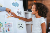 Cheerful african american girl touching picture on whiteboard near hand of psychologist on blurred background