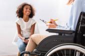 Psychologe schreibt im Rollstuhl auf Klemmbrett mit verschwommenem fröhlichem afrikanisch-amerikanischem Mädchen im Hintergrund