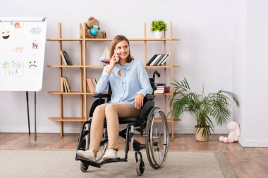 Full length of smiling psychologist talking on mobile phone while sitting in wheelchair in office stock vector