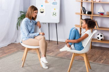Psychologist looking at african american girls embracing legs while sitting on chair during consultation in office stock vector