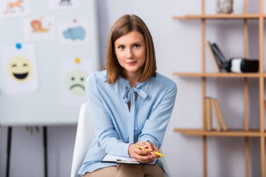 Positive female psychologist looking at camera while sitting on chair with blurred office on background stock vector