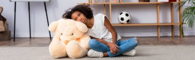 Depressed african american girl with autism looking away while leaning on teddy bear on floor near shelves in office, banner stock vector
