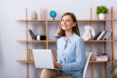 Happy psychologist looking at camera while using laptop in office on blurred background stock vector