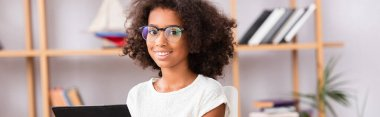 Portrait of african american girl in eyeglasses looking at camera on blurred background, banner stock vector