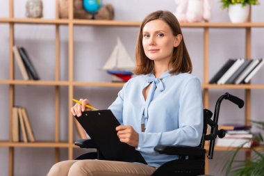 Positive female psychologist with clipboard looking at camera while sitting in wheelchair on blurred background stock vector